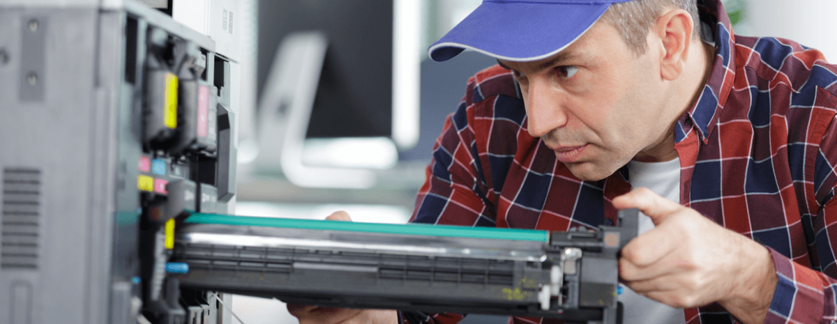 Man wearing blue hat and red flannel shirt does maintenance on printer