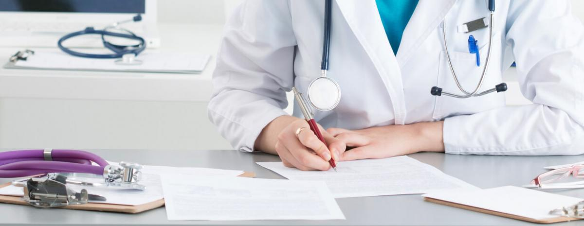 Healthcare worker writing something on paper in office