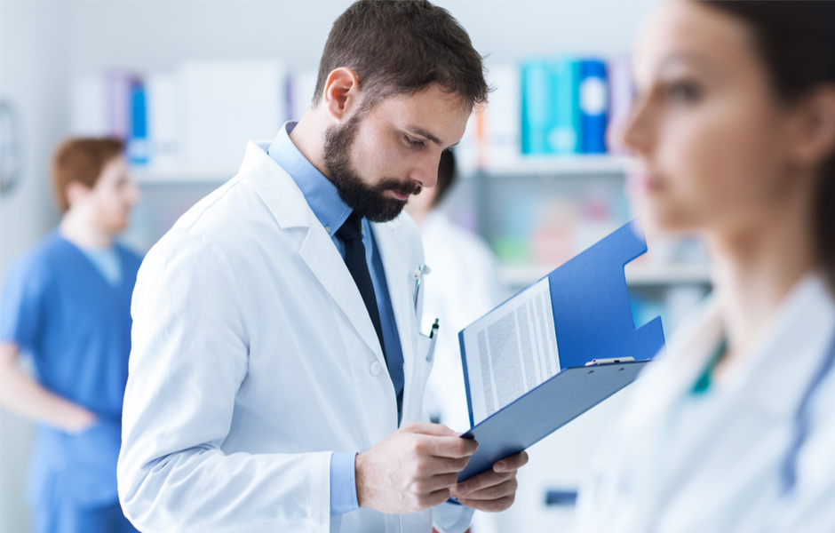 doctor looking at records in folder