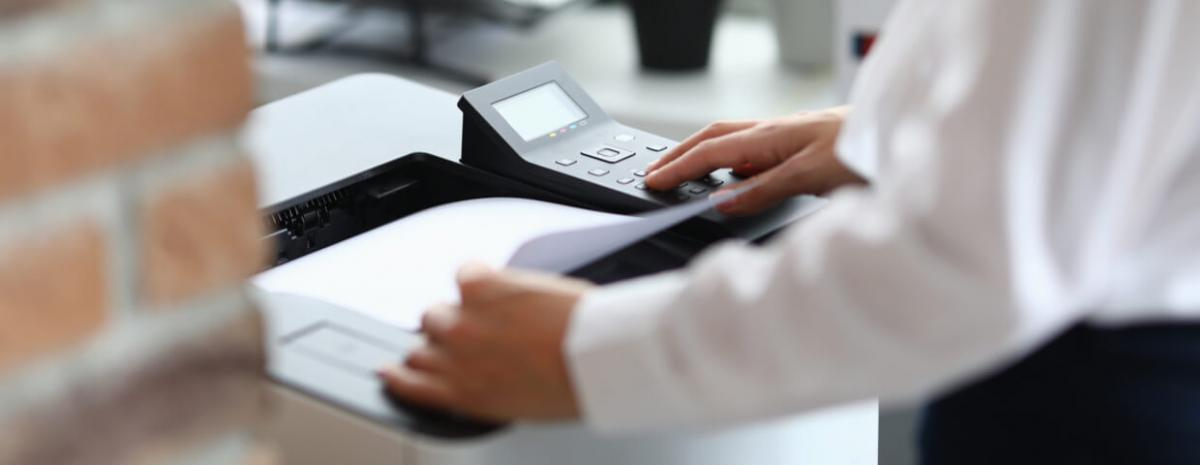 business man standing at a multifunction printer, managed print services concept