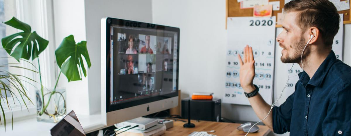 Man working from home talking to coworkers on video call