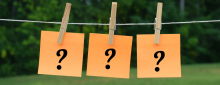 Three orange sticky notes with question marks hanging up on a clothes line in back yard