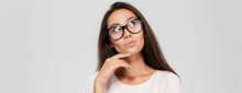 Portrait of a thoughtful young asian woman in eyeglasses looking up with hand on her chin isolated over white background