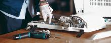 Man repairs a printer wearing gloves using a screwdriver and tools on a wooden table