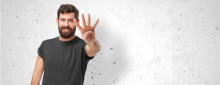 man holding up four fingers